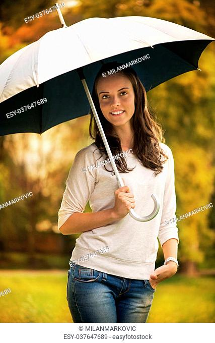 Young beautiful woman standing in rainy autumn park with umbrella