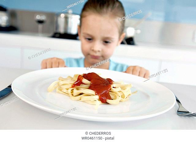 Close-up of a girl sitting at the kitchen counter in front of a plate of fettuccine