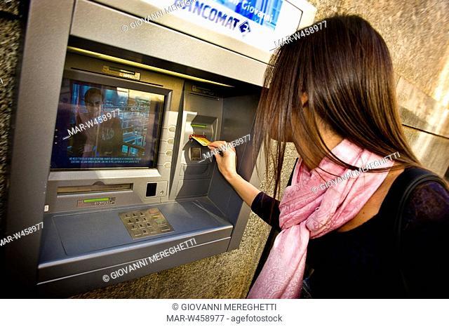 donna preleva denaro da uno sportello bancomat