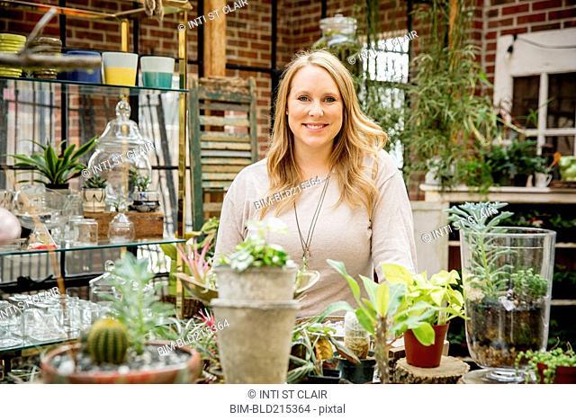 Caucasian employee smiling in plant nursery
