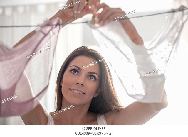 Young woman hanging up underwear to dry