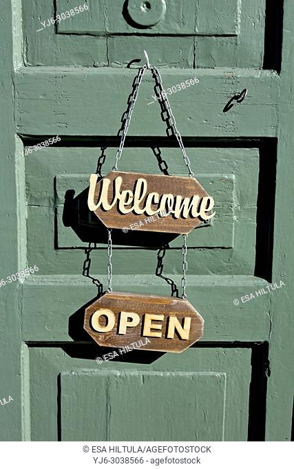 welcome and open signs on green wooden door