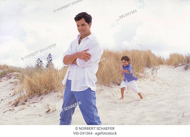 beach-scene, full-figure, man mid of 30, wearing white shirt and jeans plays with his 4 year old son bare feeted in the dunes  - GERMANY, 07/04/2004