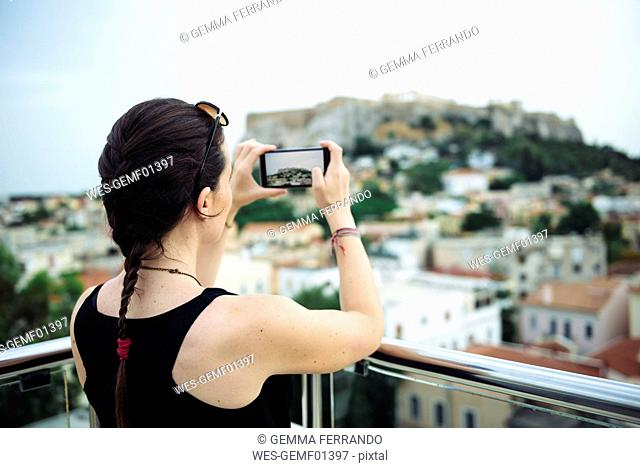 Greece, Athens, woman taking a cell phone picture of the Parthenon temple in the Acropolis surrounded by the city