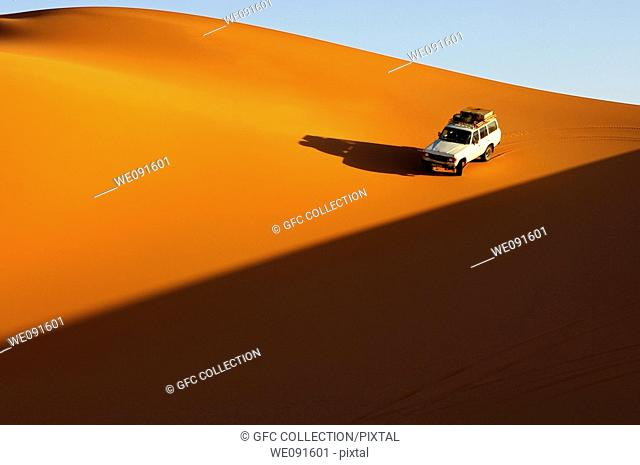 Four-wheel drive car driving at sunset on the pristine slope of a sand dune in the Erg Muzuruq of the Sahara desert, Libya