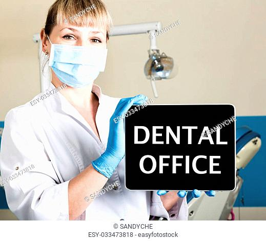 technology, internet and networking in medicine concept - femail dentist holding a tablet pc with dental office sign. at the dental equipment background