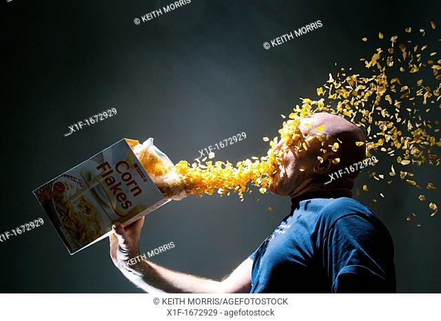 Corn flakes from a box cascading onto a man's face, conceptual image for overconsumption greed glutony