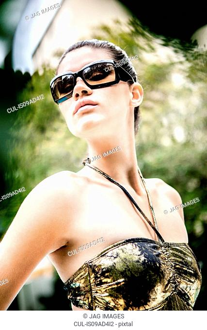 Close up portrait of young woman posing in sunglasses