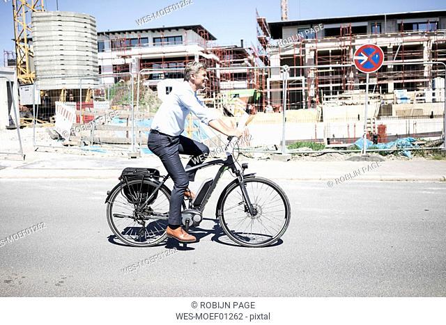 Smiling man on e-bike riding along construction site