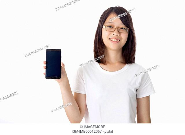 Teenage girl holding mobile phone and smiling at the camera