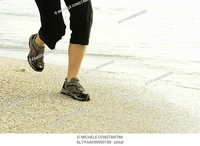Woman jogging at the beach, low section
