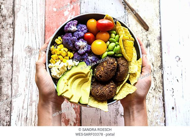 Girl's hands holding Quinoa veggie bowl of vegetables, feta, nachos and quinoa fritters