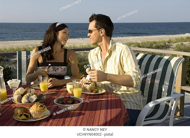 Close-up of couple eating on deck near beach