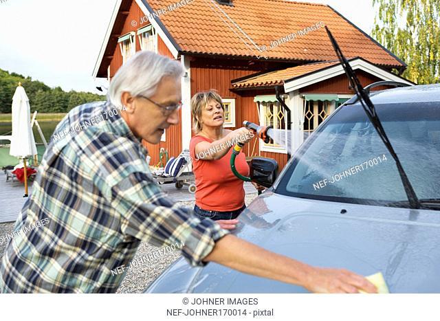 A man and a woman washing their car outside their house