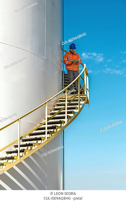 Industrial worker on stairs checking fuel storage tank using digital tablet