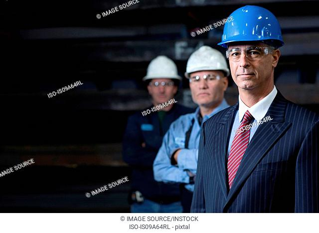 Businessmen standing in metal plant