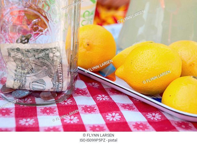Dollar bills in jar with fresh lemons