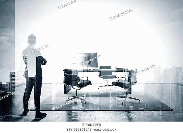 Stylish businessman in a suit looking at the horizon in office. Double exposure, black and white
