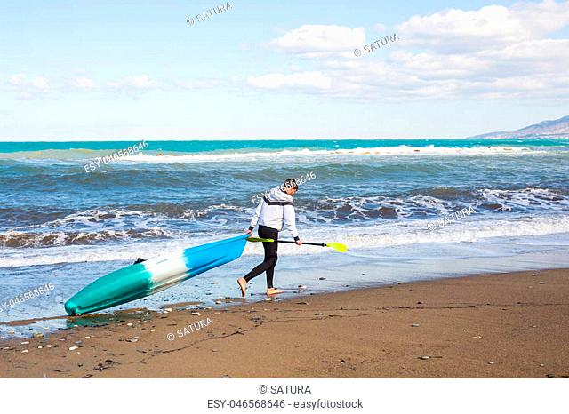 Man walking on the beach with kayak. Traveling by sea. Leisure activities on the water