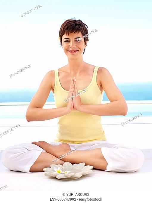 Happy young female sitting in the lotus position