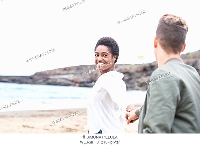 Happy young couple walking hand in hand on the beach