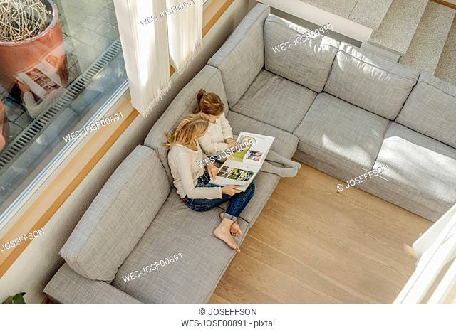 Mature woman and girl at home looking at photo album on couch