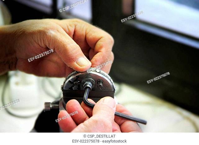 Jeweler mints silver decoration in workshop