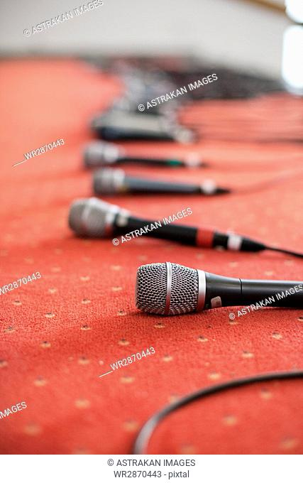 Row of microphones on red carpet at studio