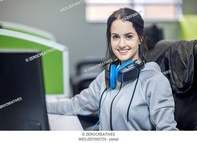 Portrait of smiling young wearing headphones in office