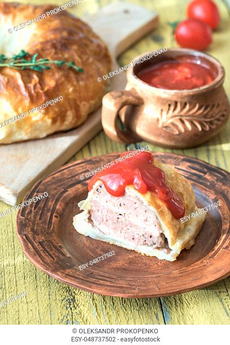 Portion of beef Wellington with tomato sauce