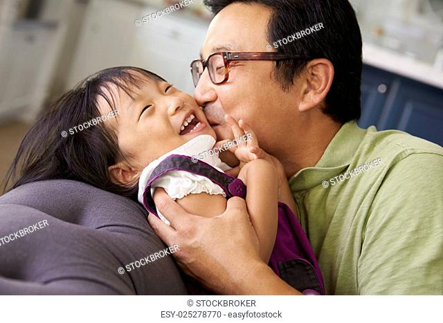Affectionate Father And Daughter Relaxing On Sofa Together