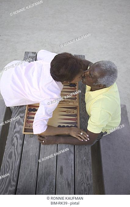 Senior couple kissing over game of backgammon