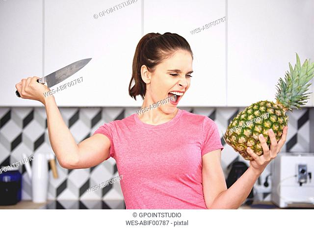 Portrait of screaming woman attacking pineapple with knife in the kitchen
