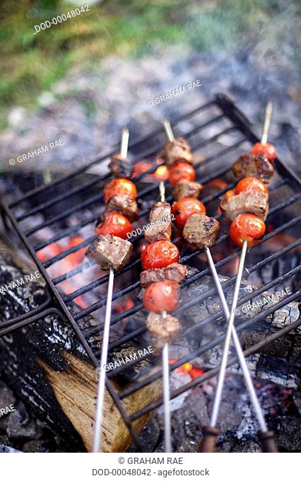 Chunks of beef and cherry tomato kebabs grilling on skewers above burning embers of camp fire