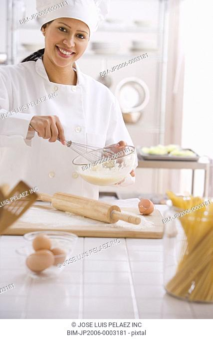 Hispanic female chef whisking batter