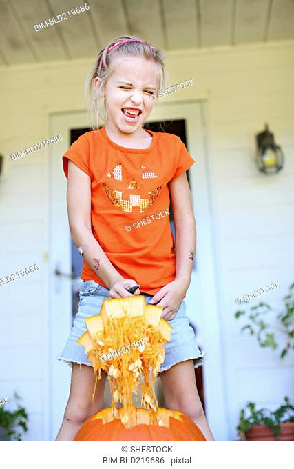 Caucasian girl carving pumpkin on front porch