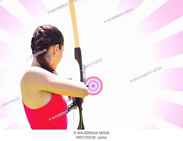Woman aiming bow and arrow at target