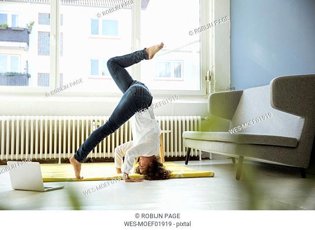 Businesswoman practising yoga on the floor