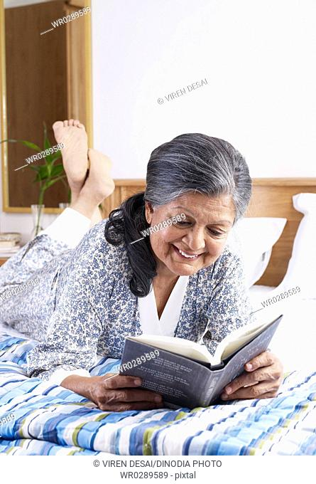 Old lady reading novel recline on bed MR702S