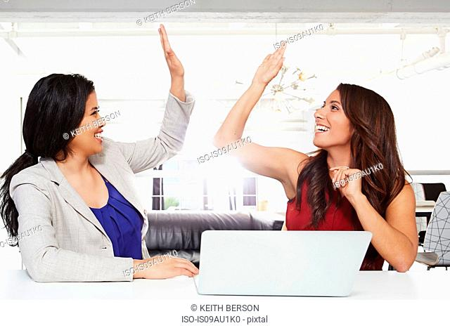 Two businesswomen sitting at desk, giving high five