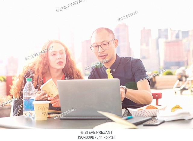 Businessman and woman looking at laptop at waterfront cafe with New York skyline, USA