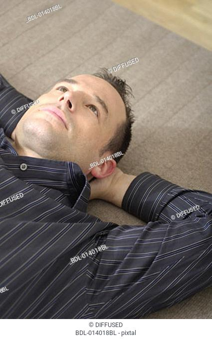 portrait of young man lying on rug with pensive expression