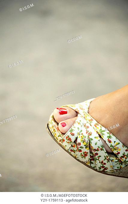 Girl with summer shoe and red nails
