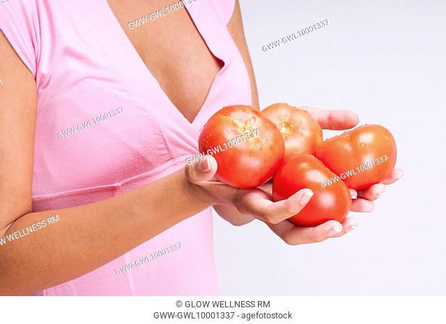 Mid section view of a woman holding tomatoes