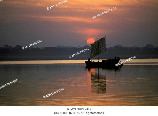 SUNRISE over a small INDIAN fishing boat on the GANGES RIVER - VARANASI BENARES, INDIA