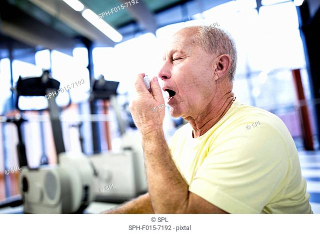 MODEL RELEASED. Senior man using asthma inhaler in gym