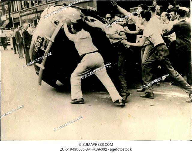 Jun. 06, 1943 - Mob Spirit At Work In Detroit Race Rioting: Passed By Censer. A car owned by a Negro is overturned by a mos of white meant at the height of race...