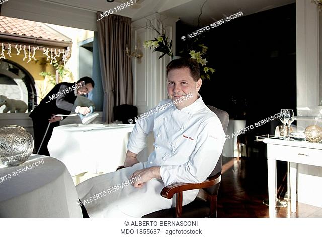 Italian chef Enrico Cerea known as Chicco sitting on a chair in a photocall shooted at his restaurant awarded with three Michelin stars 'Da Vittorio'