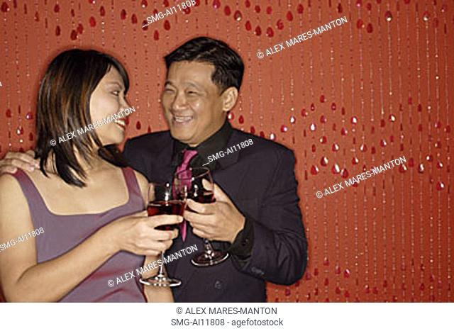 Couple looking at each other, holding wine glasses