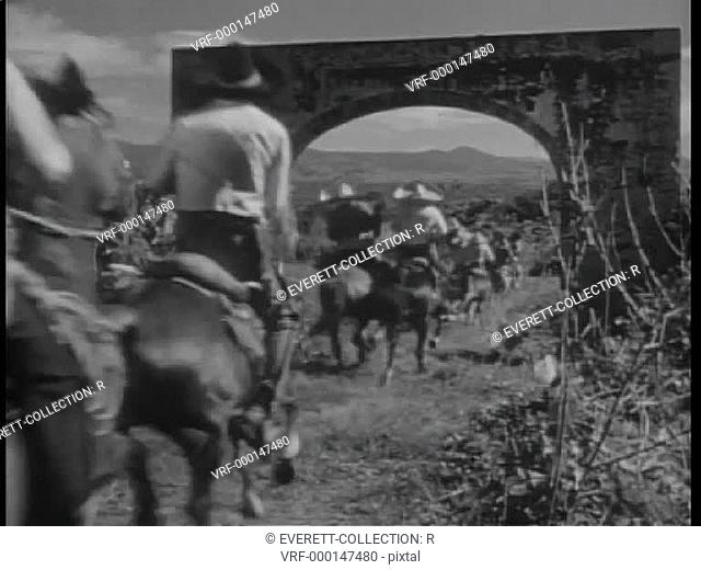 Rear view of bandits on horseback riding through archway